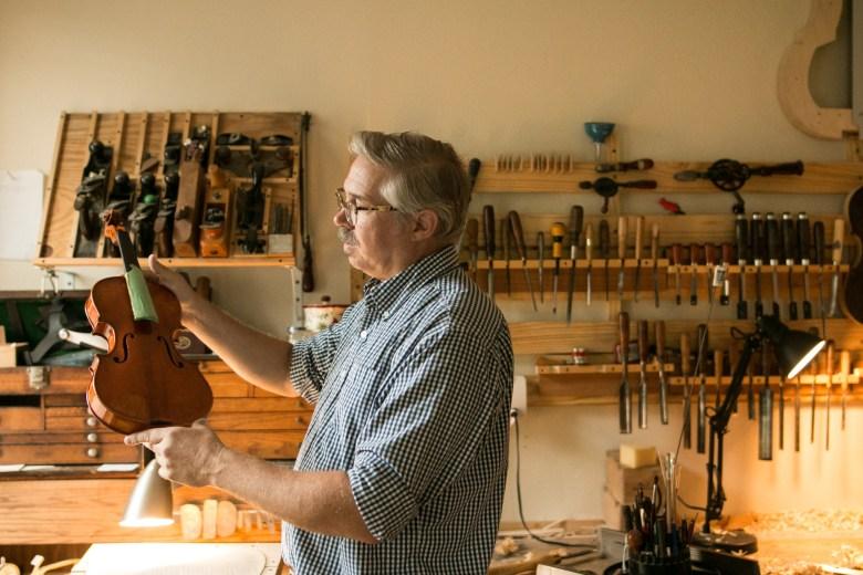 Scott Albert examines the varnish on a violin in his workshop.