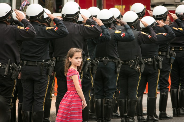 A young girl listens to a trumpet playing TAPS before the funeral of firefighter Scott Deem.