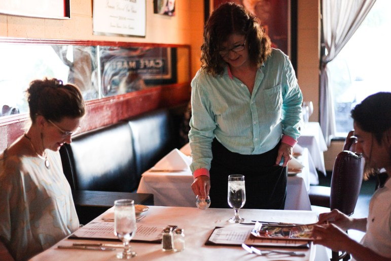 Server Nancy Richardson lights a candle for customers Chealsea Singh (left) and Louis Singh.