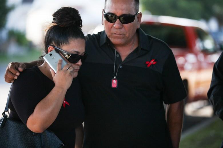Deem's cousin Liza Hernandez (left) and uncle Joe Hernandez (right) embrace outside Porter Loring Mortuary for Scott Deem's rosary.