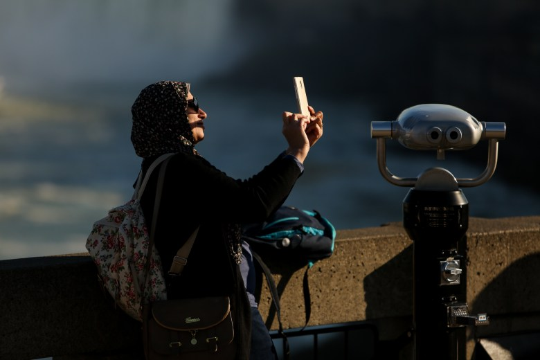 A tourist takes a selfie on an observation deck overlooking Niagra Falls.