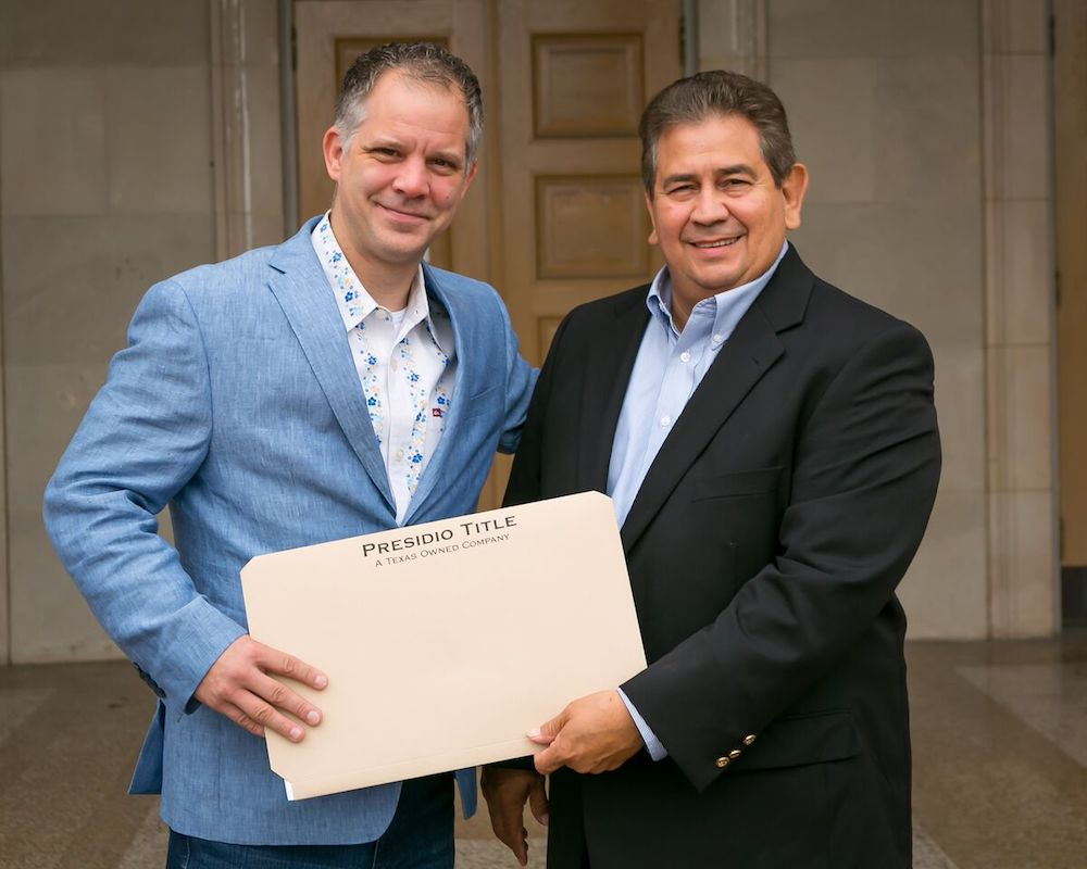 """Playhouse San Antonio CEO and Artistic Director George Green (left) and Local business owner John R. """"Rick"""" Aleman hold the title to an 8,000 sq. ft. parcel of land that Aleman donated to the theater."""