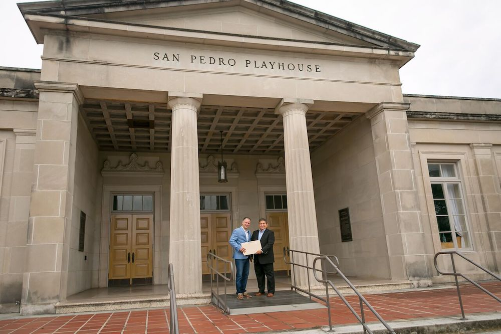 """Local business owner John R. """"Rick"""" Aleman hands over the title for land valued at $250,000 to Playhouse San Antonio CEO and Artistic Director George Green in front of the historic theater."""