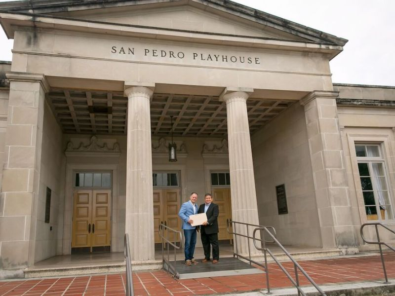"Local business owner John R. ""Rick"" Aleman hands over the title for land valued at $250,000 to Playhouse San Antonio CEO and Artistic Director George Green in front of the historic theater."