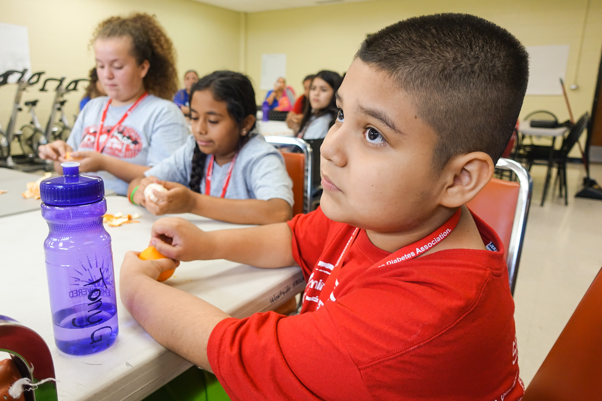 Campers peel oranges slowly during a nutrition education mindful eating class at American Diabetes Association camp.