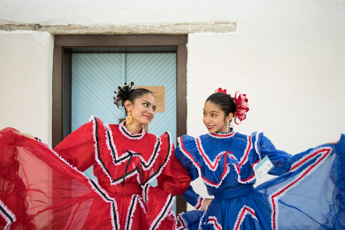 Ballet Folklorico Festival dancers (from left) Gali, 16, and Lily, 13, smile at one another at the Texas Folklife Festival.