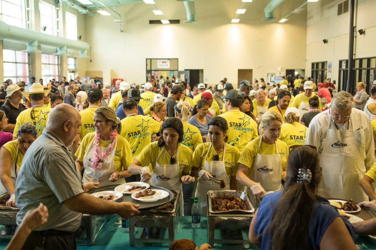 A large group of volunteers serves food at the Haven for Hope BBQ Bash.