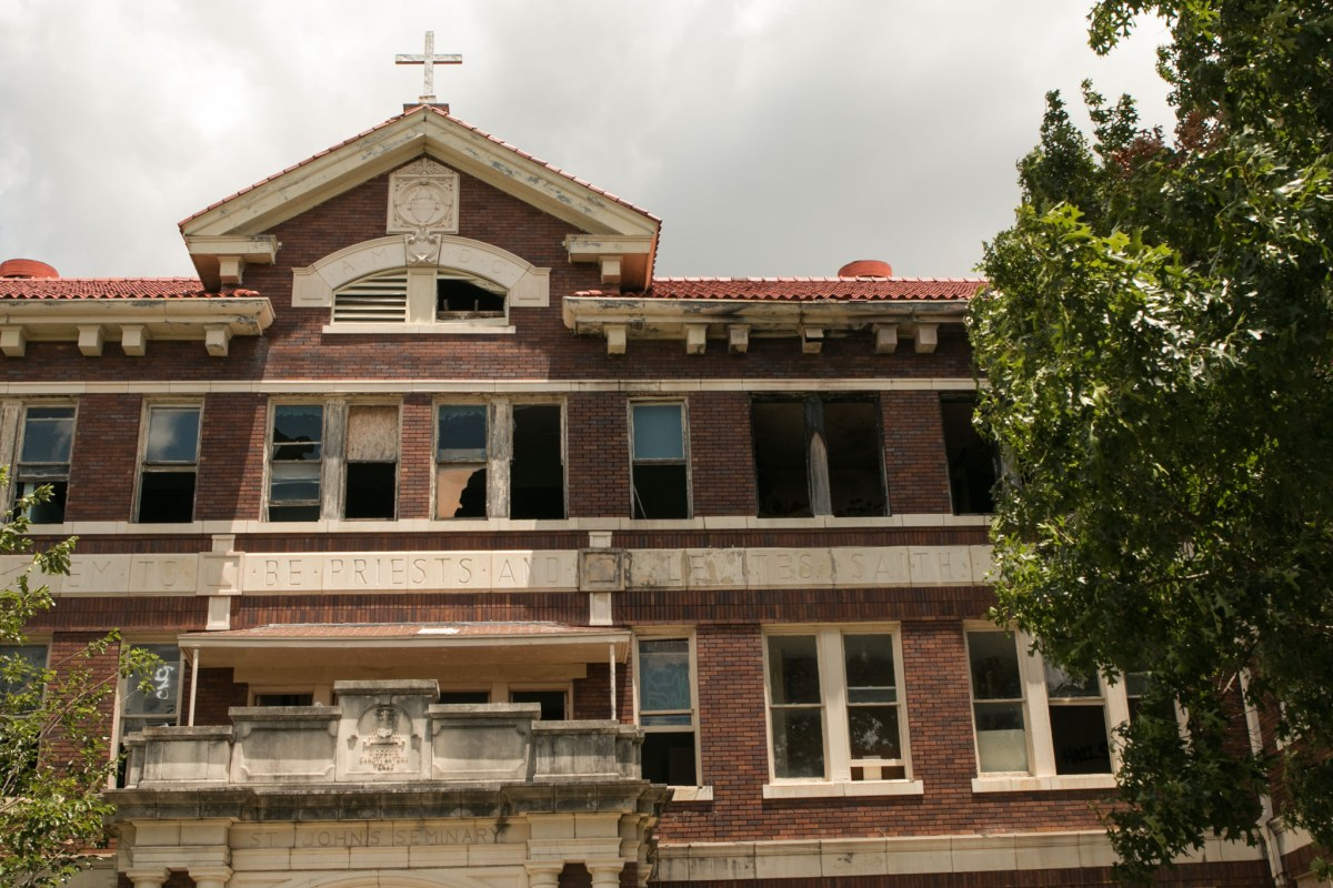 Broken and boarded up windows are visible in most of the buildings in St. John's Catholic Seminary site next to Mission Concepción.