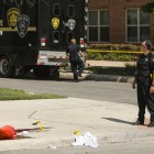 A police officer stands next to evidence marked with numbers at the crime scene on Evergreen Street and Howard Street.