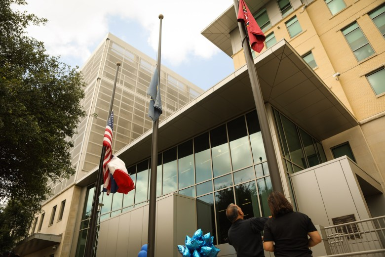 Public Safety Headquarters Officials adjust the flags to half mast after the announcement of the death of Police Officer Miguel Moreno.