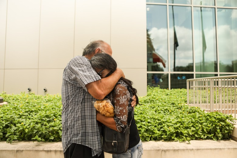 John Gomez and Cynthia Marmolejo embrace after reading the announcement of the death of Police Officer Miguel Moreno at Public Safety Headquarters.