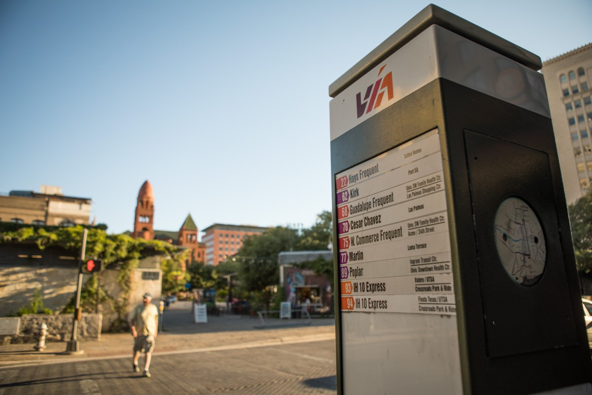 A VIA Metropolitan Transit sign marks a bus stop at the corner of Commerce Street and Soledad Street.