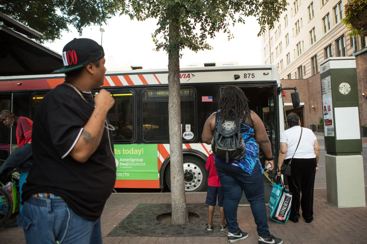 Commuters wait to board a VIA Metropolitan Transit bus at the corner of Travis Street and St. Mary's Street.
