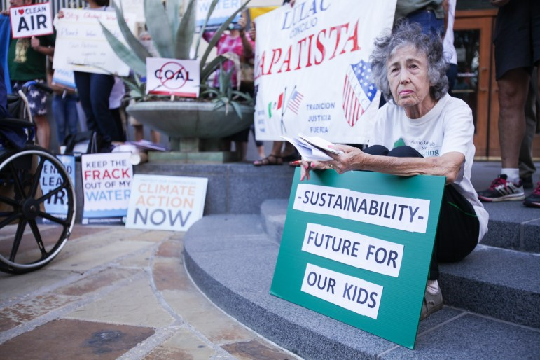 A supporter holds up a sign demanding a sustainable future for children.