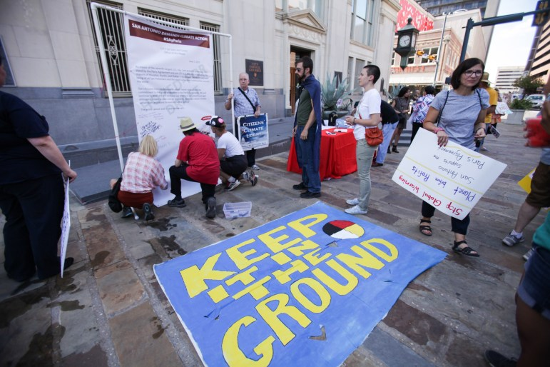 """A """"keep it in the ground"""" sign lays out in front of the declaration of support of the Paris Agreement."""