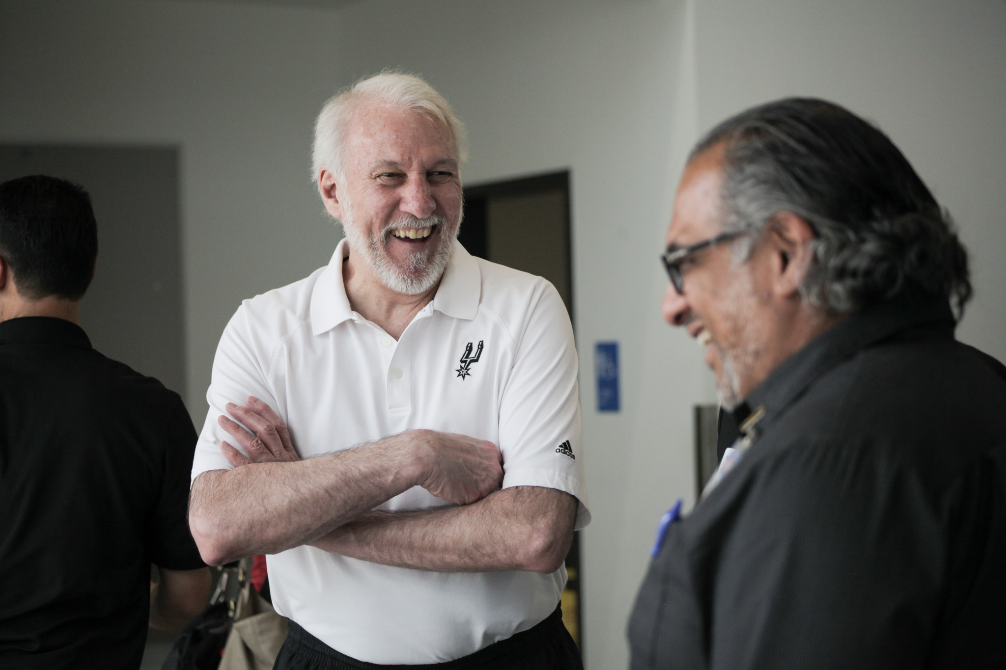 San Antonio Spurs coach Greg Popovich (left) speaks with H-E-B Media Contact Danny Flores (right) at KIPP Academy before the public discussion on the urgent need for donations to the Food Bank.