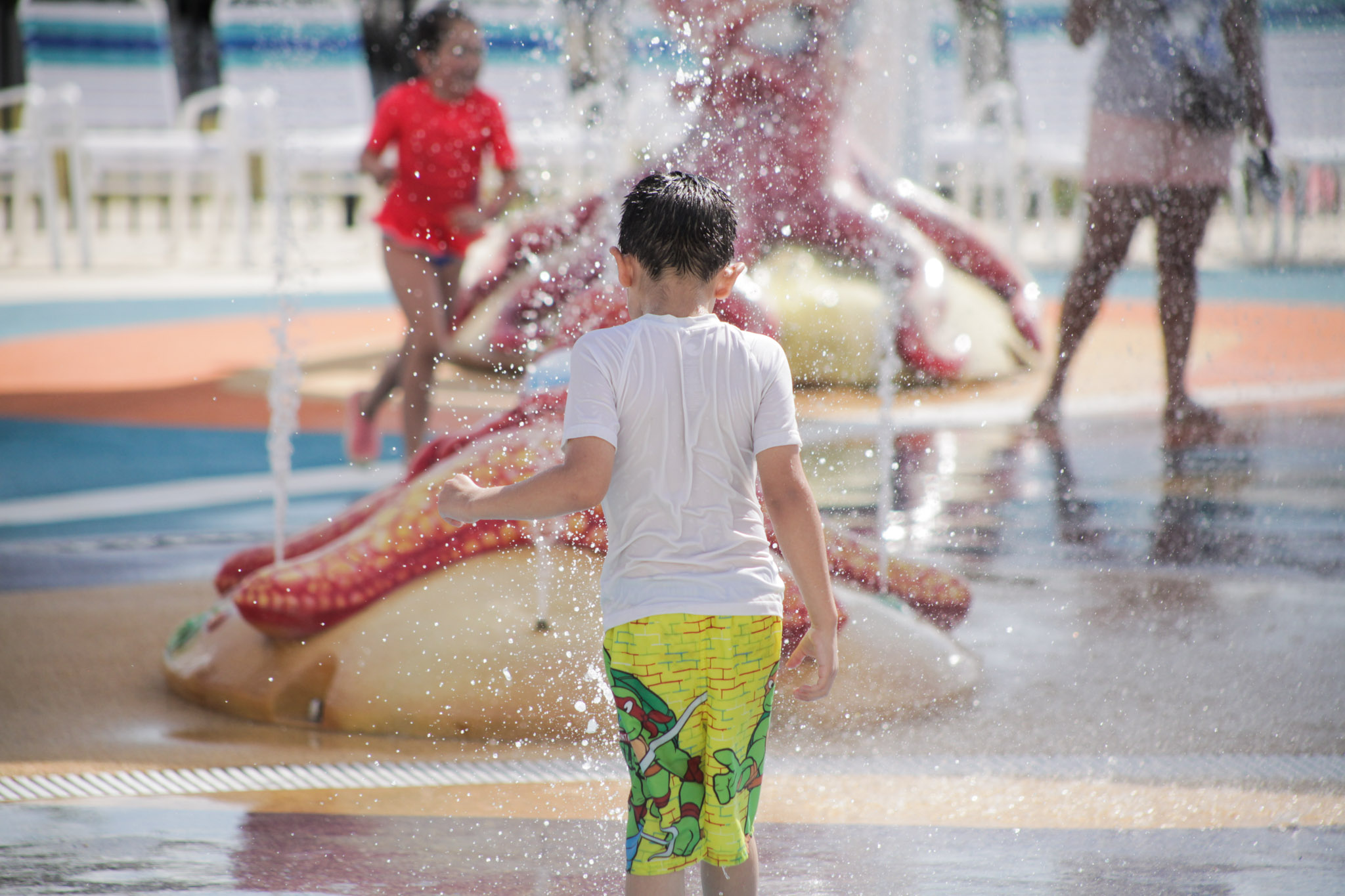 A young boy steps on the water at the new water park Morgan's Inspiration Island.