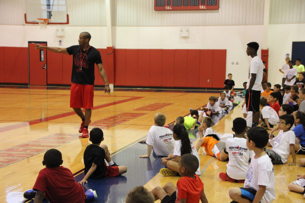 Campers listen as Antonio Daniels prepares them for the next drill at the Antonio Daniels Basketball Camp.
