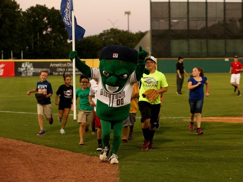 The San Antonio Missions' mascot 'Ballapeno' runs with children around the field. The San Antonio Missions mascot 'Ballapeno' runs with children around the field.