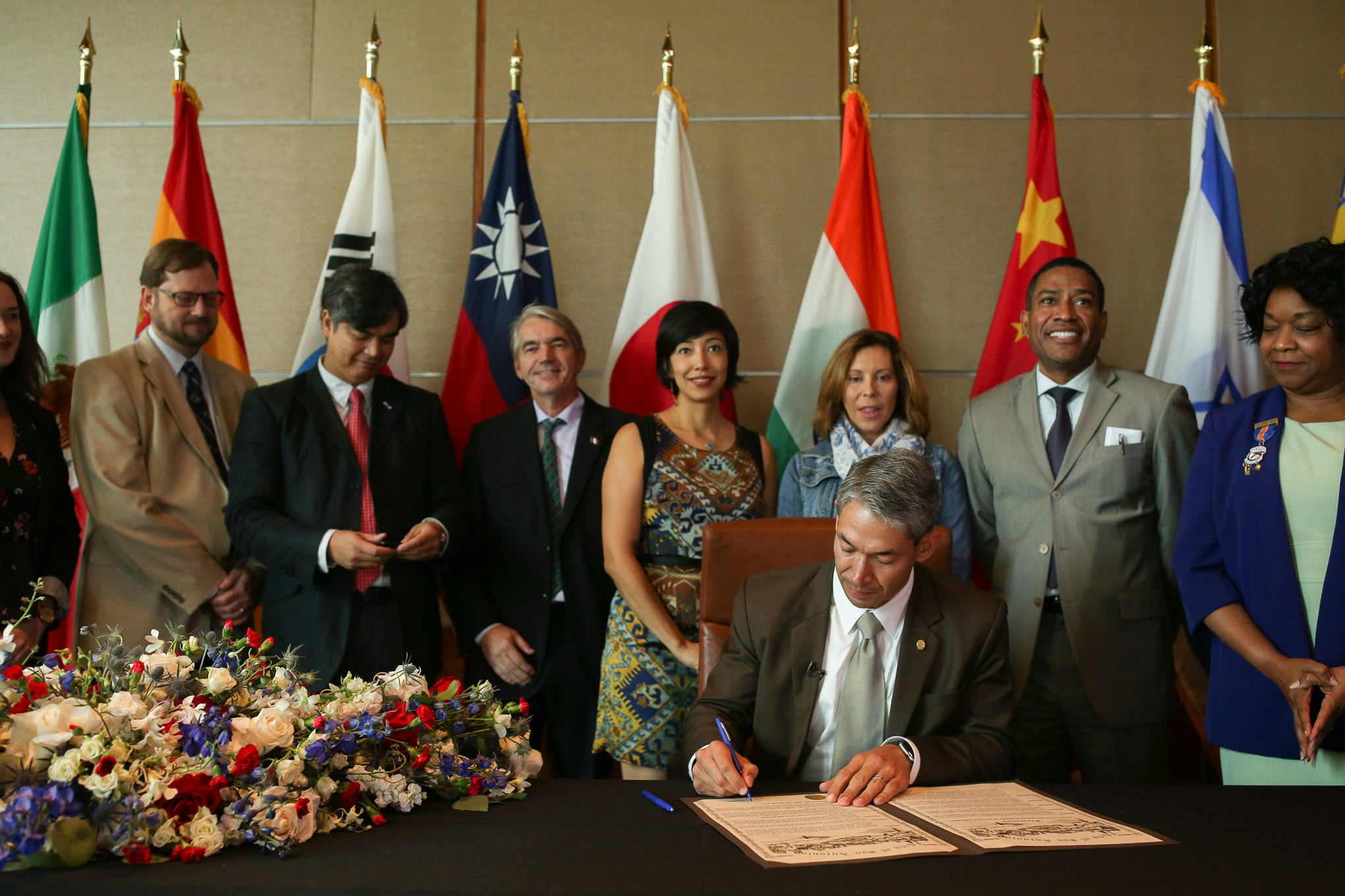 Mayor Ron Nirenberg formally signs the resolution in support of the Paris Agreement as San Antonio leaders stand behind him.