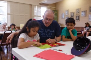 Hartmut Lau works with Jazzmin, 7, and Alex, 7 as they take turns reading individual pages.