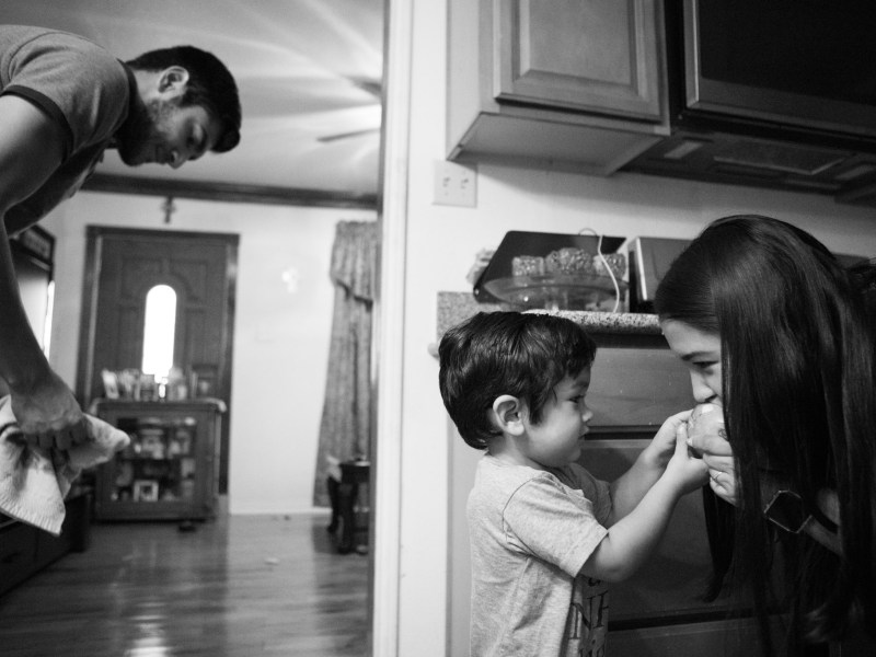 Jimmy, 2, (center) feeds his mother Alaska Martinez a pear as his father Jimmy Martinez cleans up his spit from the floor.