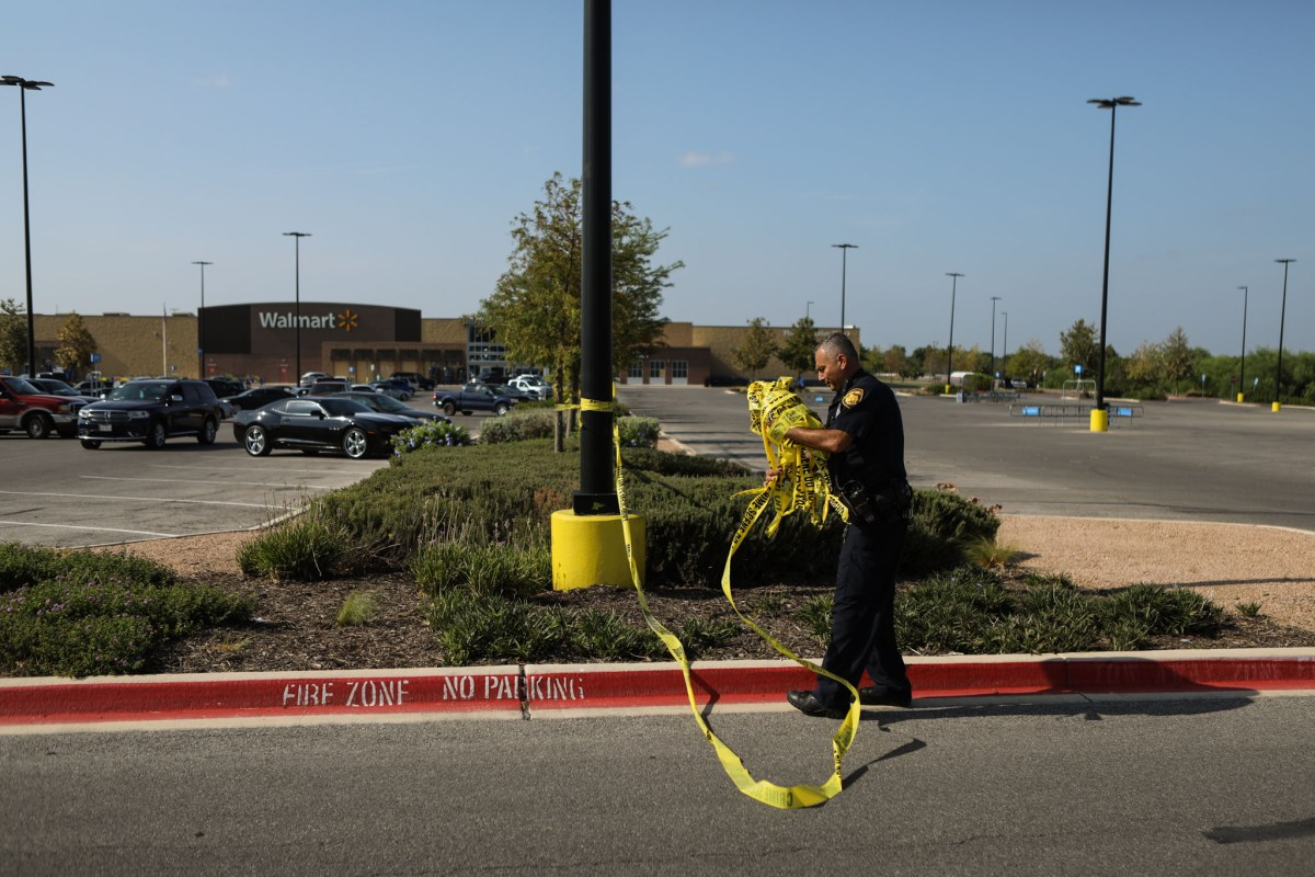 A police officer cleans up the caution tape around the area of the Walmart parking lot where the tractor-trailer was discovered.