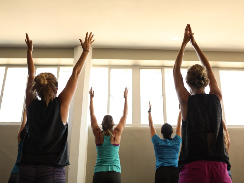 Yogis reach their arms into the air during a session of bunny yoga at Mobile Om Base Studio.