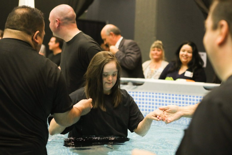 Celeste Talamantez is led into the pool where she is baptized during the 2017 convention of Jehovah's Witnesses in the Freeman Coliseum.