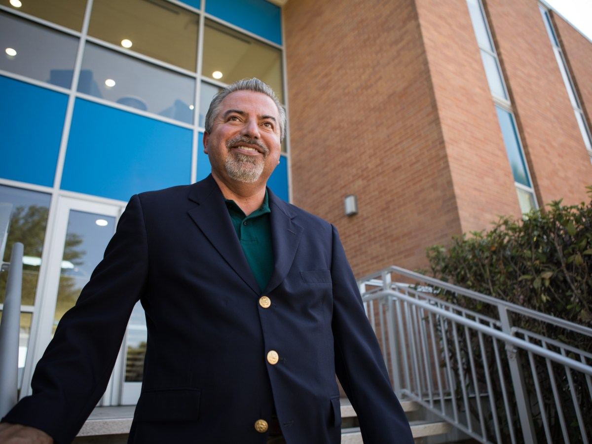 Brooks President and CEO Leo Gomez walks down the steps of the University of the Incarnate Word School of Osteopathic Medicine.