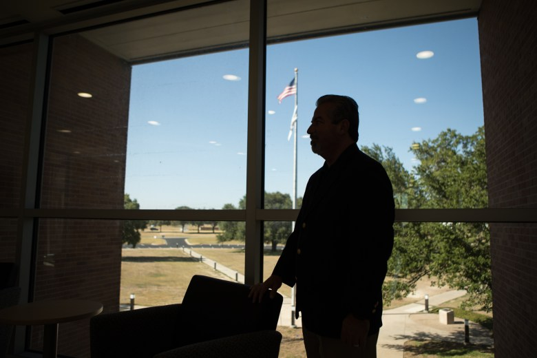 Brooks President and CEO Leo Gomez looks out the window of the University of the Incarnate Word School of Osteopathic Medicine onto the Hill.