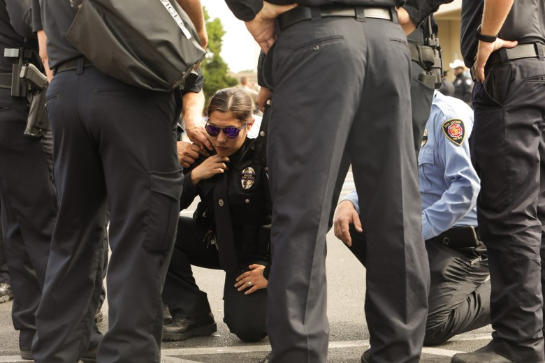 An officer kneels on the ground after becoming overheated.