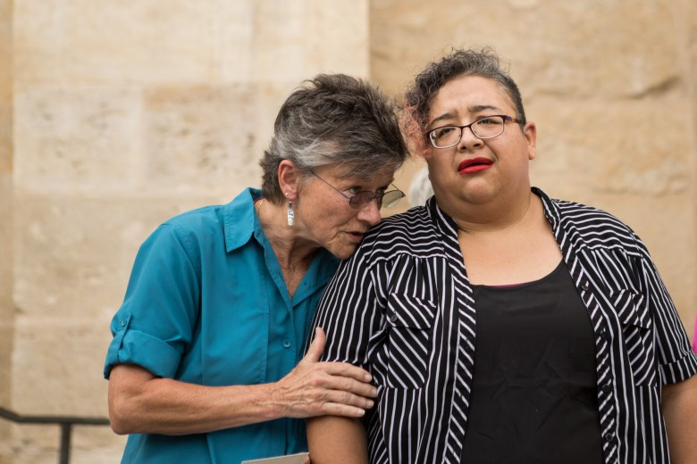 RAICES Volunteer and Esperanza Center for Peace and Justice Member Jan Olsen comforts RAICES Community Organizer Barbie Hurtado at the vigil for migrant deaths at San Fernando Cathedral.