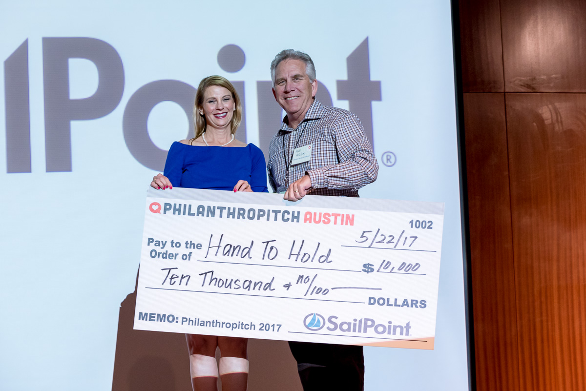 Hand to Hold founder Kelli Kelley is handed a check in the 2017 Austin Philanthropitch competition.