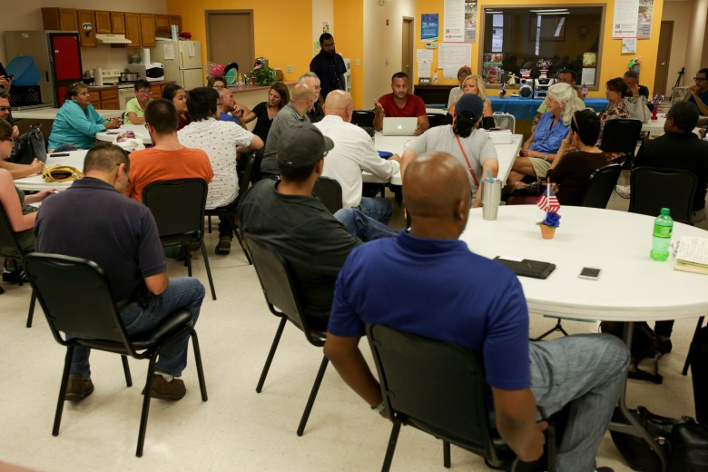 Community members and members of organizations seeking to feed and protect the homeless meet at the Ella Austin Senior Community Center.