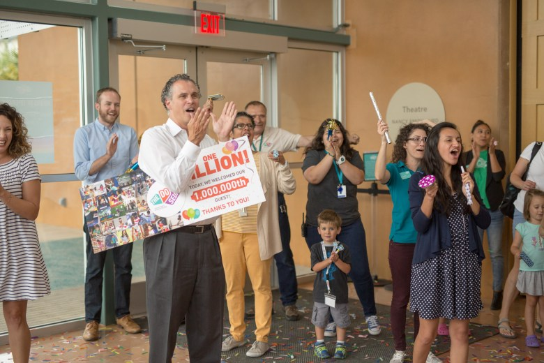 DoSeum Board Member Ty Edwards applauds along with DoSeum staff following the one millionth guest.