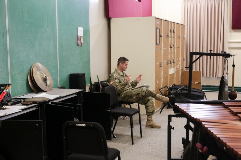 Sgt. Aaron Gutierrez follows along with the band as he sits on the side during rehearsal.