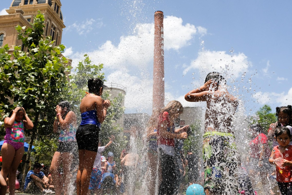 Children play in the splash fountain as they cool off during 4th of July celebrations at Pearl.