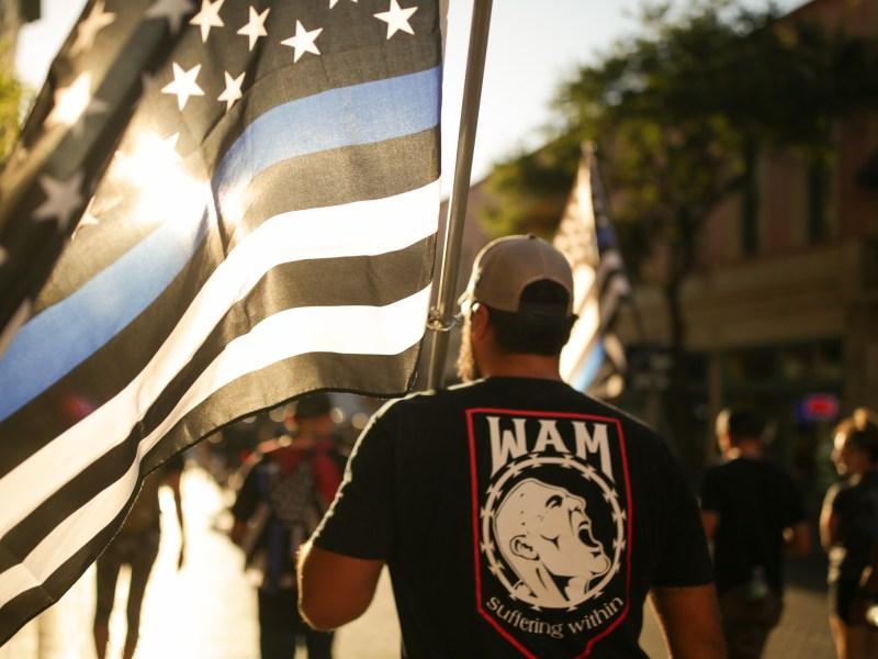 Derrick Ross of War Affected Minds carries a thin blue line flag down Commerce Street.