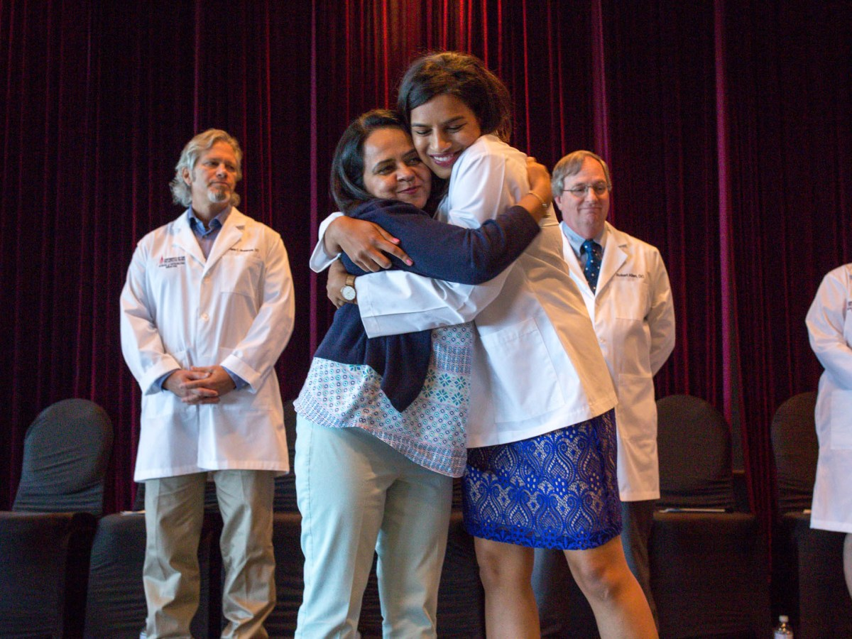 Maria Ahmad embraces her Aunt Asma Ahmad, MD following the presentation of her white coat during the ceremony.