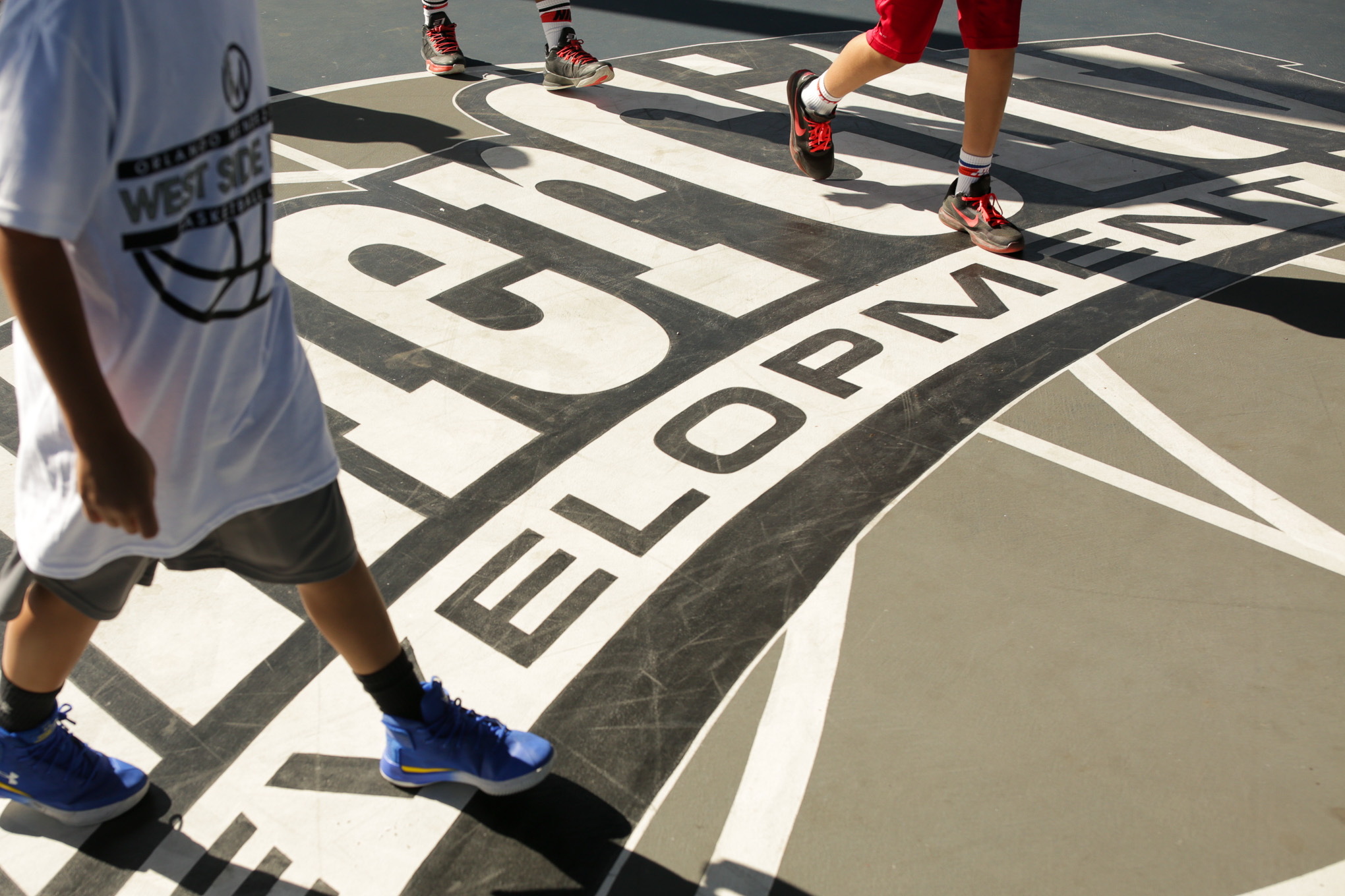 Campers walk across the InnerCity Development basketball court in the near Westside.