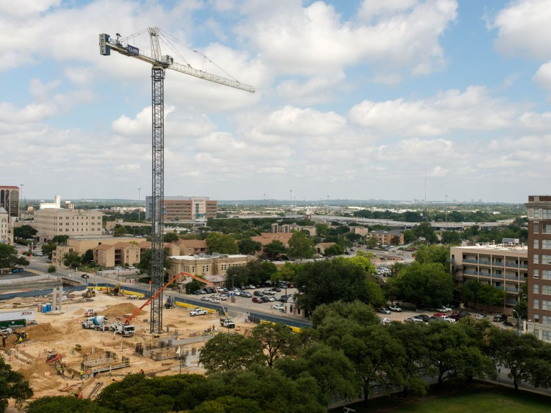 A large crane extends high above the job site of Frost Tower.