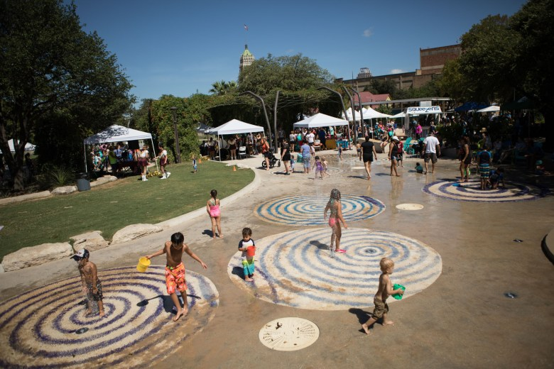 Children run through the splash pad to escape the heat at the Back to School Bash in Hemisfair Park.