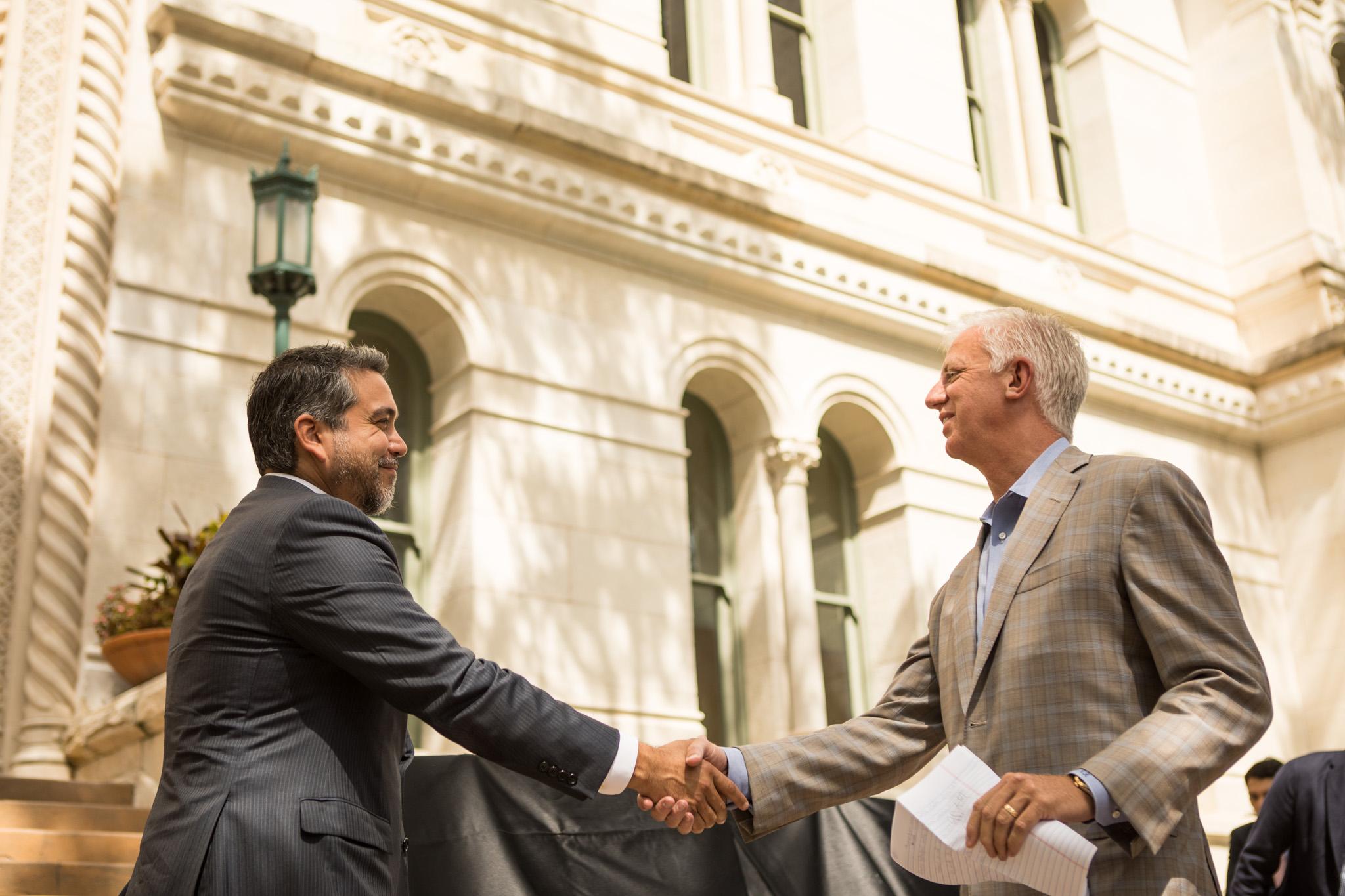 Councilman Roberto Treviño (D1) (left) shakes the hand of Gordon Hartman Family Foundation Founder Gordon Hartman at the announcement of the winner of City Hall For All Design Competition.