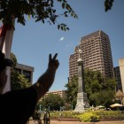 Bobby Farrell, in opposition to the removal of the Confederate monument, holds up a peace sign towards the Confederate monument in Travis Park.