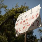 A sign is displayed in opposition of the removal of the Confederate monument in Travis Park.