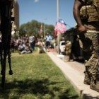 Demonstrators in opposition of the removal of the Confederate monument in Travis Park carry rifles and Confederate flags.