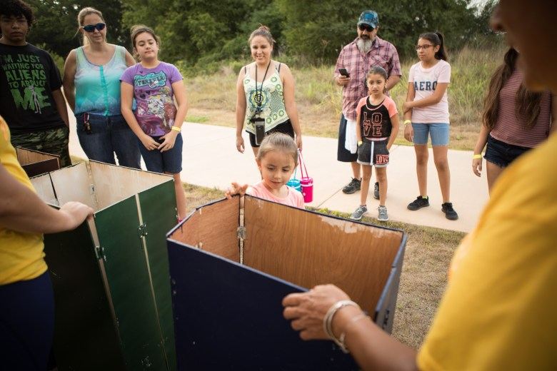 """Bella, 4, places an object into a """"recycling bin"""" as part of an activity to learn about the proper way to dispose of waste at Family, Fishing and Friends at Acequia Park."""