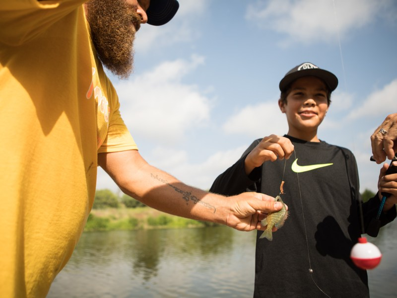 Fin Addict Angler Foundation Volunteer Eric Stevens (left) helps Brooks, 10, with his caught fish at Family, Fishing and Friends at Acequia Park.