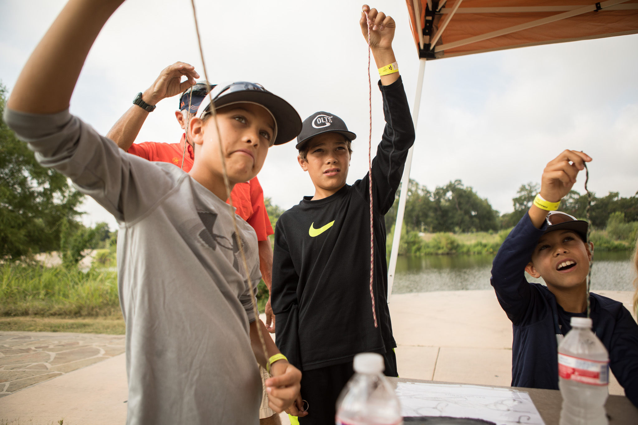 (From left) Dylan, 10, Brooks, 10, and Jake, 9, hold up fishing line during a lesson in knot tying at Family, Fishing and Friends at Acequia Park.